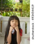 Small photo of An Asian girl rest one's chin on two's hands absent -minded with a beautiful black long hair sitting on the ladder wearing a black and red t- shirt with a blurry background
