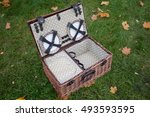 A Wicker Picnic Basket On Gree...