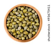 Small photo of Capers in wooden bowl on white background. Edible flower buds of Capparis spinosa, caper bush or Flinders rose. Pickled caper buds are used as seasoning or garnish. Isolated macro food photo close up.