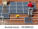 worker installing solar panels on roof - stock photo