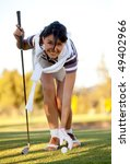 Woman placing a golf ball on the course - stock photo