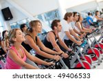 Group of gym people on machines - stock photo
