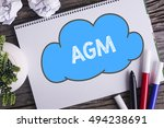 Small photo of Notepad and green plant on wooden background with AGM word
