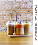 Small photo of Smoothies and iced coffee in plastic cup on wooden tray and brick wall background in cafe. Take away drinks concept.