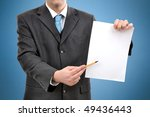 Businessman is holding a piece of blank white paper, business presentation scene - stock photo