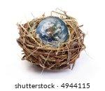 Earth globe in bird's nest over white background - stock photo