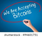 Small photo of Women Hand writing We Are Accepting Bitcoins with black marker on visual screen. Isolated on blue. Business, technology, internet concept. Stock Photo