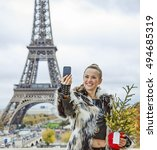 Small photo of The Party Season in Paris. happy trendy fashion-monger with Christmas tree in fur coat in Paris, France taking selfie with phone