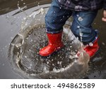 Kid In Red Rubber Boots Make O...