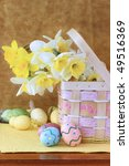 Easter eggs and daffodils in a pretty basket. Shallow DOF. - stock photo
