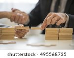Small photo of Teamwork or building bridges concept with a businessman and woman holding wooden building blocks to form a bridge over a gap while clasping hands in the background.