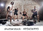 Small photo of Group of fit and muscular people practicing with barbell on urban place
