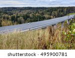 Elevated highway viaduct, steel concrete roadway bridge, speed road crossing russian forest. - stock photo