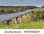 Steel girder bridge on reinforced concrete pillars, four-lane highway crosses the Russian forest, sunny summer day. - stock photo