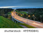 Overpass and light trails at night on the illuminated highway in forest. - stock photo