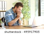 Small photo of Side view of an ill entrepreneur sneezing in a wipe at office near a window
