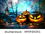Small photo of Halloween pumpkins on wood in front of nightly spooky forest background