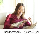 happy woman reading a magazine... | Shutterstock . vector #495936121