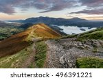 Stock photo rocky path on catbells on an autumn morning with sunlight hitting mountain and vibrant sunrise 496391221