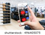Small photo of Augmented reality marketing concept. Hand holding smart phone use AR application to check number of social media like and sale price in retail fashion shop