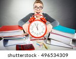 Small photo of Paper work against time. Young expressive woman in office with big red clock. Crazy happy businesswoman close to ending her work.
