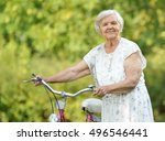 Senior Woman With Bike In Park...