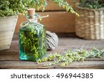 Small photo of Bottle of absent or tincture of tarragon, absinthe healing herbs on old wooden table. Herbal medicine.