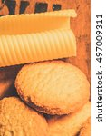 Small photo of Close up of fresh baked cookies with piece of butter lying on wooden bakehouse bench