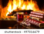 Small photo of Glass mug of hot drink or alcoholic drink or mulled red wine and antique books in front of warm fireplace. Magical relaxed cozy atmosphere near fire. Autumn or winter concept