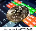 Golden bitcoin coin against digital currency chart, shallow depth of field - stock photo