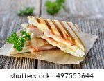 Pressed and toasted double panini with ham and cheese served on sandwich paper on a wooden table