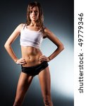 Young sexy sporty woman. On wall background. - stock photo