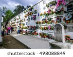 Small photo of San Lazaro Cemetery, Antigua, Guatemala - November 2, 2014: People decorate crypts of deceased family members with wreaths & flowers on All Souls' Day in Spanish colonial town of Antigua.
