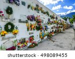 Small photo of San Lazaro Cemetery, Antigua, Guatemala - November 2, 2014: Flowers & wreaths cover mausoleum on All Souls' Day in Spanish colonial town of Antigua.