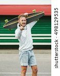 Small photo of Sanguine hipster man standing with longboard on his shoulder