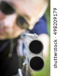 Small photo of Man takes aim with a hunting rifle closeup.