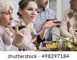 Small photo of Young, elegantly dressed woman talking at the dinner table, accompanied by her relatives