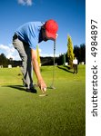 male golfer taking the ball out from the hole - stock photo