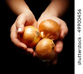 female hands holding three brown onions - stock photo