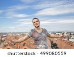 Small photo of Utopic portrait of young man with his arms open over blue sky and city landscape