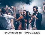 Stock photo enjoying amazing party group of beautiful young people dancing with champagne flutes and looking 499233301