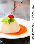 Small photo of White airy cream-mousse dessert with syrup, cherry, mint on dark wooden background.