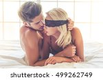 Stock photo beautiful passionate couple is having sex on bed man is holding a lace bandage on his beautiful 499262749