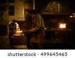 Small photo of Blacksmith forging the molten metal on the power hammer in smithy