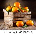 wooden box of fresh mandarin... | Shutterstock . vector #499880311