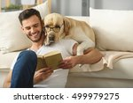 Stock photo handsome guy holding book while smart pet read it 499979275