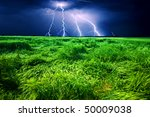 Lightning strike over a green field