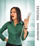 Surprised young business woman talking on the phone - stock photo
