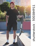 Small photo of Young man holding skateboard. Skater standing outdoors. My sport is my passion. Against the grain.