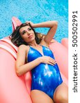 Small photo of Beautiful pregnant woman, wearing swimsuit, lying on a pink flamingo air mattress in a pool of blue water, summer